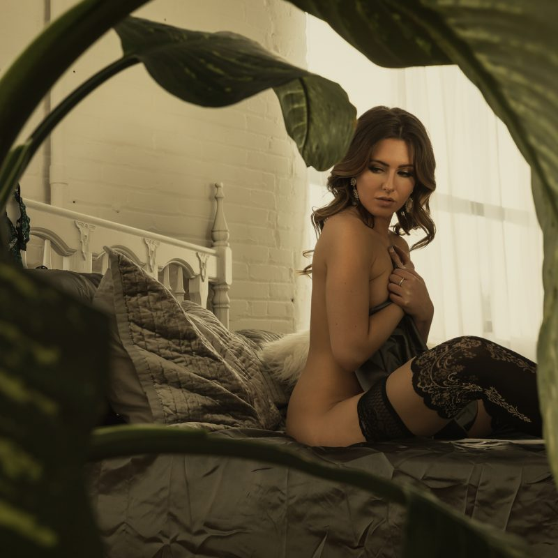 implied nude voyeur styled boudoir image on a bed